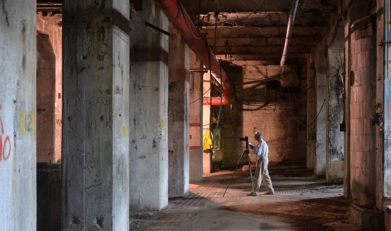 Le bénévole Bill Woodley travaille parmi les imposants piliers de béton au sous‑sol qui, autrefois, supportaient les machines massives de l'usine se trouvant à l'étage.