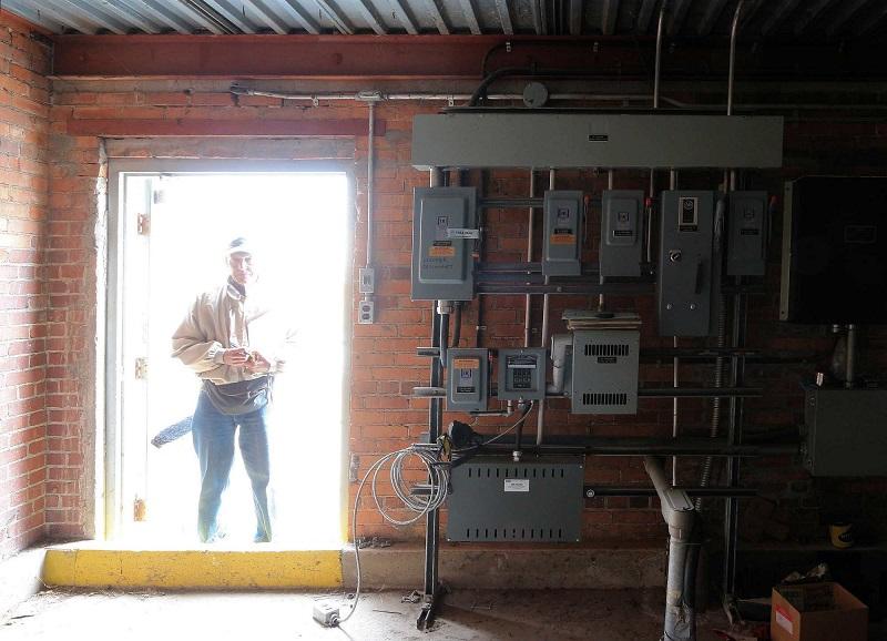 Caje Rodriquez, photographe bénévole, tient une planchette à pince retenant des rapports et paraît plutôt redoutable debout dans le cadre de la porte de la salle des commandes électriques située sur le toit.