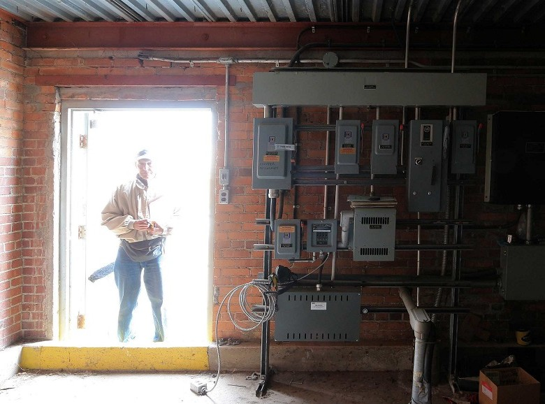 Volunteer photographer Caje Rodriquez, with a clipboard of log sheets in hand, looks rather fiercesome in the doorway of a rooftop electrical room.